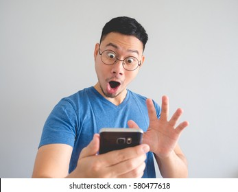 Happy Asian man using smarphone with shocked  and surprised face expression.