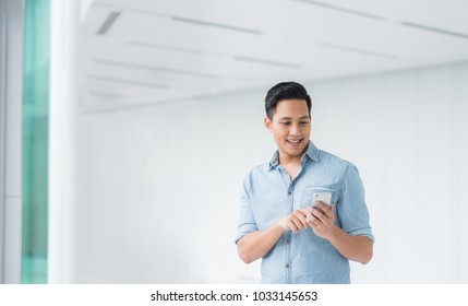 Happy Asian man using smartphone mobile in modern building