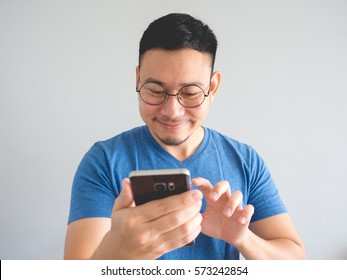 Happy Asian man using smartphone with face expression.
