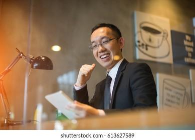 happy asian man using tablet