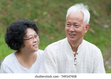 Happy Asian mature couple relaxing at outdoor park on a summer day.