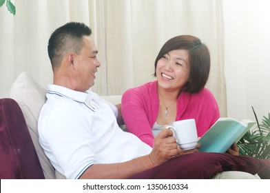 Happy Asian Middle age couple looking at the book and relaxing with a cup of coffee