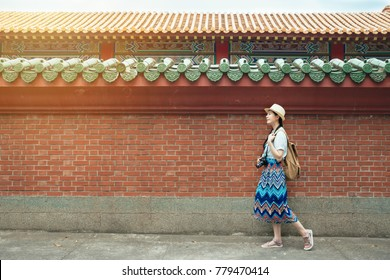 Happy Asian mixed race woman tourist having fun walking in traditional imperial chinese temple red brick wall background. Girl enjoying China travel destination.