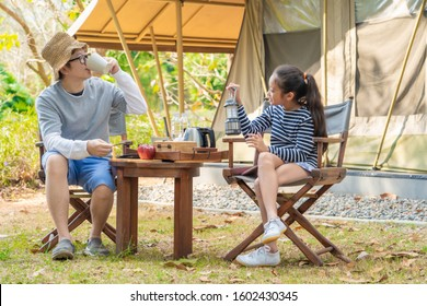 Happy Asian mom and daughter enjoy camping together at countryside
