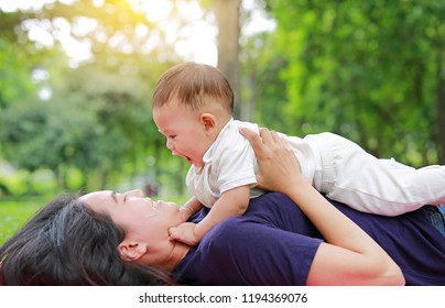 Happy Asian mom embrace her son lying in the green garden. Funny mother and infant baby boy playing in summer park.