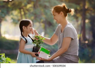 Happy Asian mother cleaning her daughter's face, Plant together