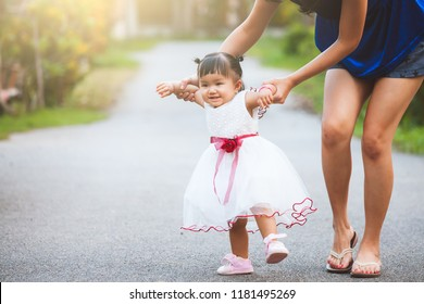 Happy asian mother and cute little baby girl walking together with fun and love