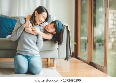 Happy asiatische Mutter und süße kleine Tochter, die Spaß beim Spielen und Umarmungen zu Hause im Wohnzimmer hat