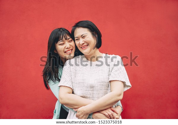 Happy Asian mother and daughter having fun outdoor - Chinese family people spending time together outside - Love, relationship and parenthood lifestyle concept