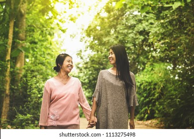 happy Asian mother and daughter holding hand walking outdoors in a beautiful nature park smiling to each others