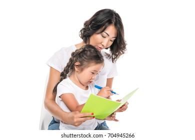 happy asian mother and daughter writing in copybook, isolated on white