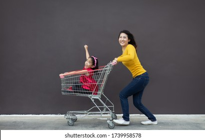 happy asian mother and daugther love shopping action with shopping cart on blank background.