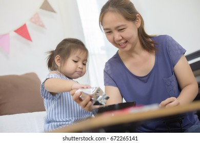 Happy Asian mother feeding delicious cornflake for her daughter