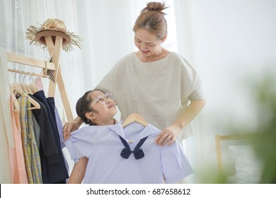 Happy Asian mother helping daughter dressing her's uniform prepare to school, Back to school
