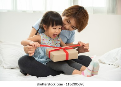 Happy Asian mother and her daughter unwrapping gift box.  Mum and girl smiling and hugging on bed in their bedroom togetherness.
