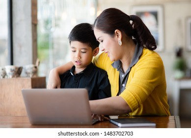 Happy Asian mother and her son using laptop at home. - Shutterstock ID 1483702703