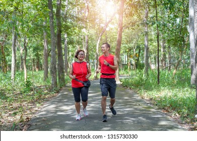 Happy asian mother and son jogging running in the park, Elderly care exercise sport activity concept