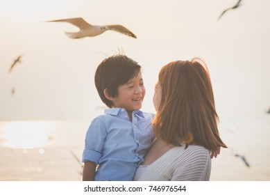 Happy Asian mother and son playing on the beach