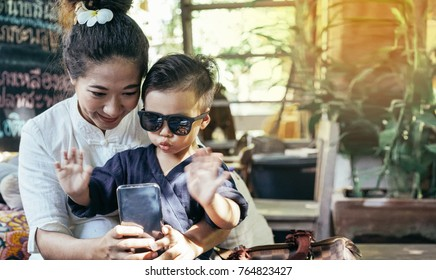 happy asian mother and son using smartphone