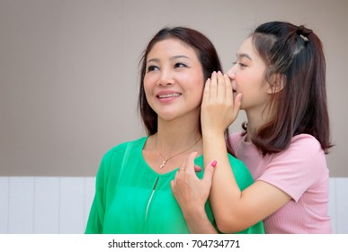 Happy Asian mother and teen daughter whispering gossip