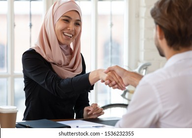 Happy asian muslim businesswoman hr manager employer wear hijab handshake hire male applicant make contract deal with partner collaborate shake client hand at job interview business meeting concept