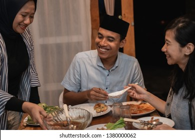 happy asian muslim family dinner together at home. break fasting or buka puasa on ramadan kareem