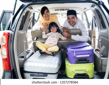 happy asian muslim family with kid sitting in the car trunk with suitcase ready for road trip for eid mubarak holiday
