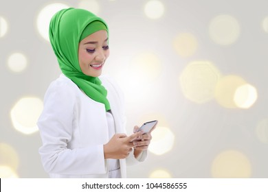 Happy asian muslim woman holding a phone over blur light background