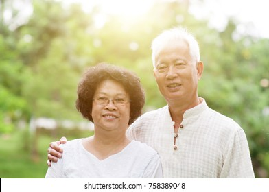 Happy Asian old couple smiling at outdoor park on a sunny day.