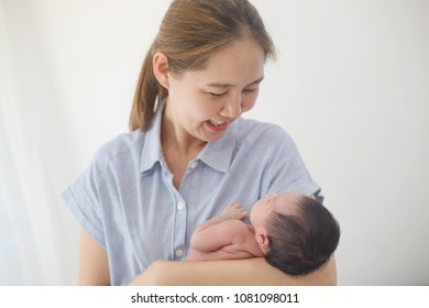 Happy Asian other take care her adorable newborn baby carefully