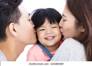 happy asian parents kissing little girl