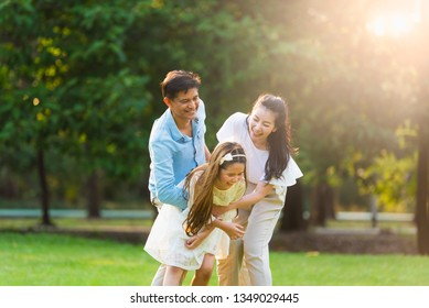 Happy asian playing enjoy funny family time in park with sunlight sky background.