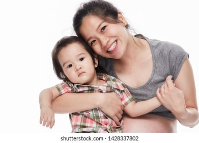 Happy asian pregnant woman hugs with her young boy on the white background.