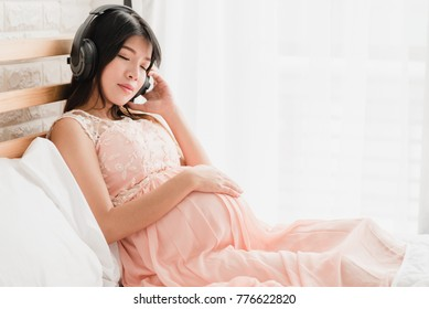 Happy Asian pregnant woman sitting on the bed listen to music in headphones