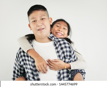 Happy Asian pretty girl enjoying riding on her brother piggyback, lifestyle concept.