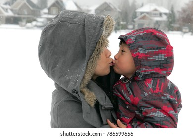 Happy asian pretty young mother and her son play together during winter holidays outside in snow park
