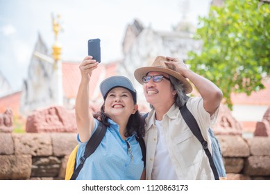 Happy asian retired couple taking their photo by smart phone at a temple in Thailand
