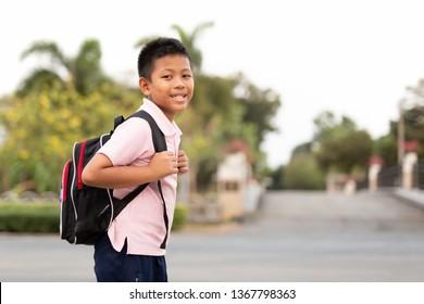 Happy asian school boy in uniform with backpack walking back home.