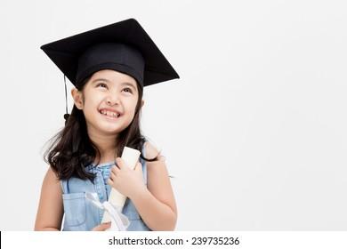 Happy Asian school kid graduate in graduation cap looking up