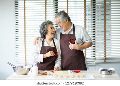 Happy Asian senior couple in brown aprons are holding red cookies cutters in heart shape over their chest. Looking each other. Having Fun.