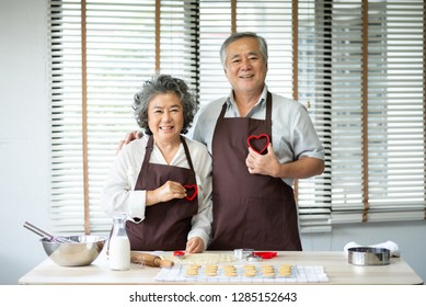 Happy Asian senior couple in brown aprons are holding red cookies cutters in heart shape over their chest. Looking at the camera.