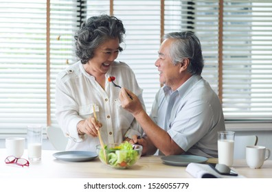 Happy Asian Senior couple doing and eating healthy salad at their house together. Lover, Retirement, Wellness.