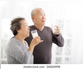 happy asian senior couple drinking milk