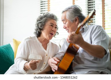 Happy Asian senior Couple enjoying with singing and playing guitar together. Having fun with the wedding Anniversary. Copy space.