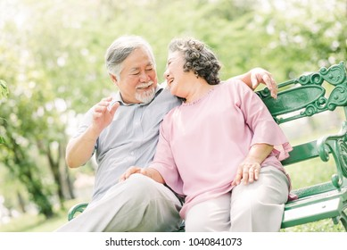 Happy Asian senior couple having a good time. They laughing and smiling while sitting outdoor in the park.