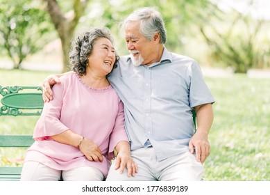 Fröhliches asiatisches Seniorenpaar, das sich gut amüsiert. Sie lachen und lächeln, während sie draußen im Park sitzen