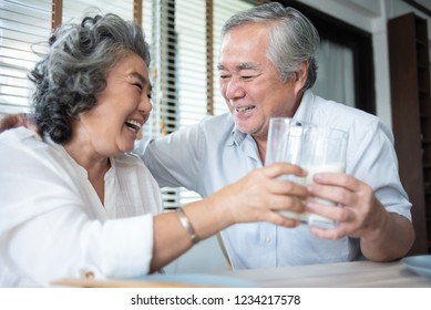 Happy Asian Senior Couple laughing and drinking milk from the glasses together on the morning.