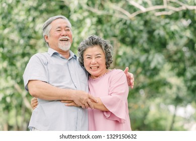 Happy Asian senior couple laughing and smiling while holding each other outdoor in the park.