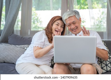 Happy Asian Senior Couple  lifestyle technology device concept,Lovely elderly couple using laptop computer vdo call with Their family
