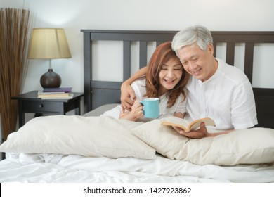 Happy Asian Senior Couple  lifestyle after retiree concept,Lovely elderly couple reading a book on bed